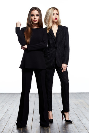 Two beautiful sexy woman pretty face makeup wear fashion style clothes black suit pants jacket accessory and shoes dress code glamour model office businesswoman catalog trend design white background. Stock Photo
