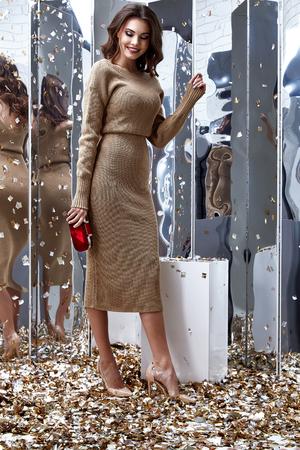 De sexy mooie vrouw van het mannequin donkerbruine haar draagt de schoenstijl van de beige lange kleding voor de vakantie van de partijvakantie verjaardag kleedt organische natuurlijke van de achtergrond pailletten make-up dame lichaamshuid zorg bijkomende zak. Stockfoto