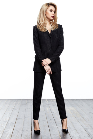 Beautiful elegant business woman blond hair wear style fashion formal dress code black suit pants and jacket pretty lady clothes office meeting white background collection heath boss secretary. 免版税图像
