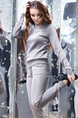 Sexy beautiful woman long curly brunette hair wear casual grey comfortable clothes for every day knitted suit wool cashmere sport pretty face makeup mirror and sequins party celebrate have fun.