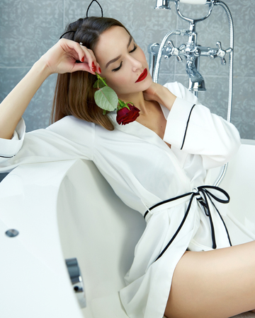 Beautiful young sexy woman with dark hair, evening make-up, red lips and manicure sitting in the bathroom in a white silk robe, holding a red rose smiling white teeth, Valentines Day Stock Photo