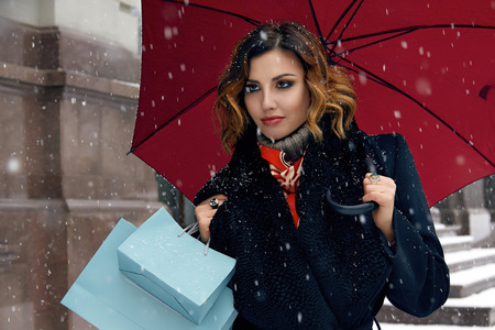 Beautiful sexy young woman with curly brown hair with bright makeup wearing a black coat walking on snow-covered streets past shops with red umbrella and gift packs for Christmas and New Year Winter Stock Photo - 95047126