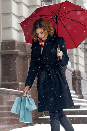 Beautiful sexy young woman with curly brown hair with bright makeup wearing a black coat walking on snow-covered streets past shops with red umbrella and gift packs for Christmas and New Year Winter Stock Photo