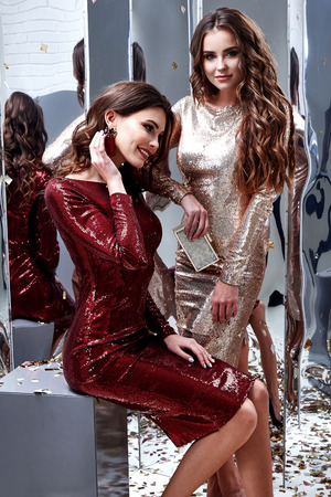 Two sexy beautiful woman wear skinny gold red dress shiny sequins style party celebrate New Year Christmas beauty salon brunette makeup jewelry model lux fashion clothes glamour girlfriend mirror. Banco de Imagens