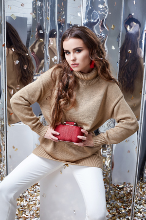 Beautiful woman sexy perfect pretty face makeup wear beige wool cashmere sweater and skinny white pants accessory bag earrings casual clothes for party office holiday celebrate brunette fashion style. Stock Photo - 95286192