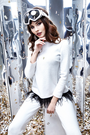 Sexy beautiful woman brunette hair wear goggles extreme mountain suit white color casual pants sweater casual sport clothing winter spring collection smile face makeup accessory studio party equipment. Archivio Fotografico - 95286202