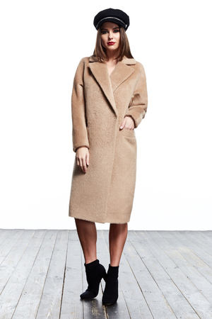 Beautiful sexy woman wear clothes for businesswoman office style outerwear casual wool cashmere coat hat girl with dark hair white background fashion catalog autumn high heels lady perfect face makeup.