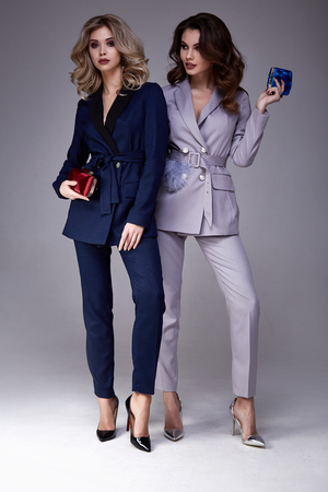 Two beautiful glamour sexy woman friend colleague wear formal dress coat suit jacket pants fashion shoes accessory bag natural beauty perfect body shape clothes meeting walk party date casual office. Archivio Fotografico