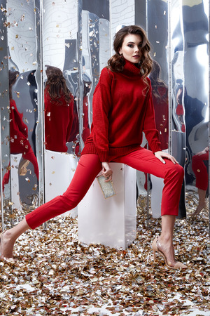 Interior design mirror wall sequins on the floor fashion model woman wear dressed casual style clothing red sweater pants spring collection accessory bag brunette party jewelry Saint Valentines Day.