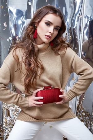 Beautiful woman sexy perfect pretty face makeup wear beige wool cashmere sweater and skinny white pants accessory bag earrings casual clothes for party office holiday celebrate brunette fashion style. Stock Photo - 96456275