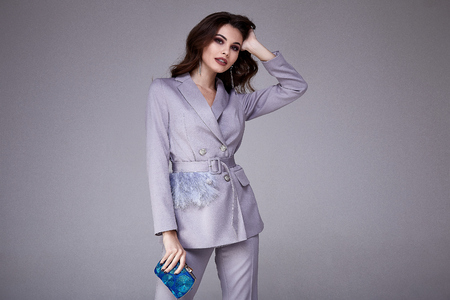 Beautiful woman lady spring autumn collection glamor model business office fashion clothes wear formal dress code style lilac color suit jacket pants accessory bag pretty face hair background studio.