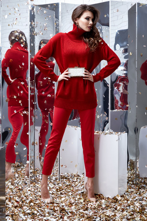 Beautiful sexy pretty woman business brunette wear red sweater pants casual style clothes party fashion model pose accessory hand bag interior design room mirror sequins shine Saint Valentines Day. Stock Photo