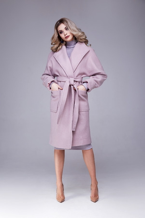Beautiful sexy woman wear clothes for businesswoman office style casual girl blond hair grey background studio fashion catalog spring dress pink coat lady perfect face and body makeup meeting walk.
