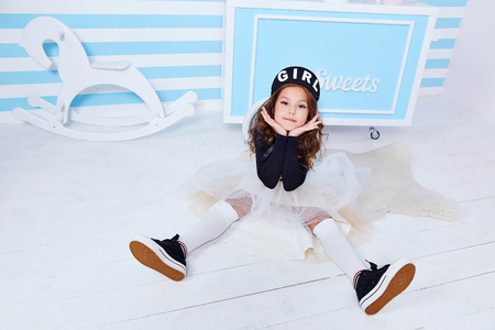 Small little girl sit on the floor beautiful lady curly hair child wear funny clothes skirt t-shirt hat beret cute face smile sweets baby shower party candy bar game room birthday fun happy play toy. Stock Photo