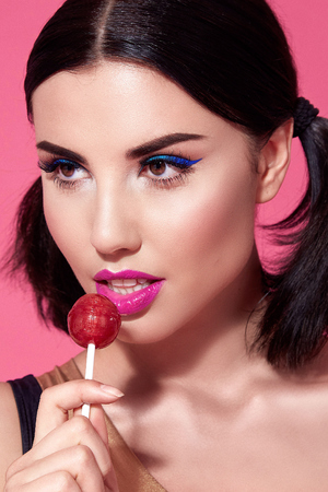 Close portrait of sexy beautiful woman brunette hair style perfect bright makeup mascara pink lipstick background face care cosmetic accessory jewelry sweets lollipop diet beauty salon white teeth. Stock Photo