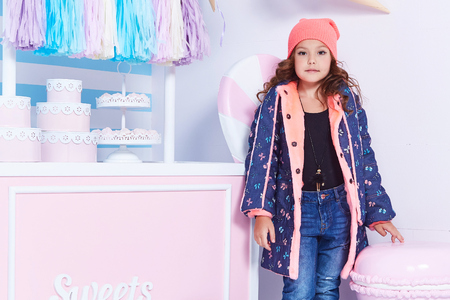 Small little girl beautiful lady curly hair child cute face smile sweets baby shower party candy bar game room birthday wear funny clothes hat jacket denim jeans toy play fun hold pillow star clothes. Stock Photo - 97104210