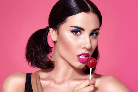 Closeup portrait of sexy beautiful woman brunette hair style perfect bright make up mascara pink lipstick background face care cosmetic accessory jewelry sweets lollipop white teeth plastic surgery.