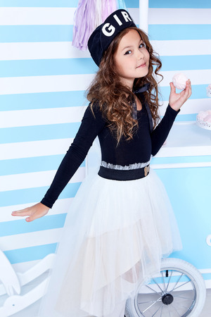 Beautiful lady curly hair small little girl child funny cute face smile sweets baby shower party candy bar game room birthday wear white skirt black t-shirt beret hat socks clothes blue strip wall. Stock Photo