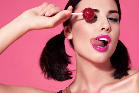 Portrait of sexy beautiful woman brunette hair style perfect bright make up mascara pink lipstick background face care cosmetic accessory jewelry sweets lollipop close one eye show tongue white teeth. Standard-Bild
