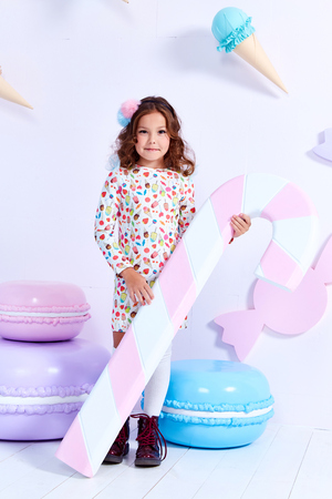 Small little girl beautiful lady curly hair child wear funny clothes dress socks boots cute face smile sweets baby shower party bar game room birthday hold big candy lollipop macaroons toy play fun. Stock Photo