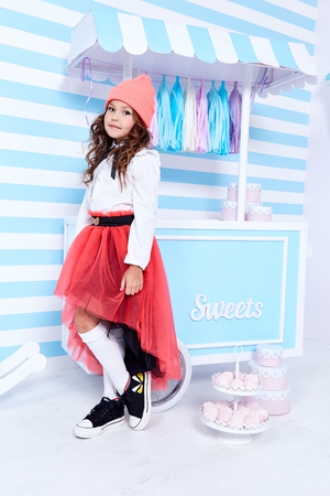 Small little girl beautiful lady curly hair child wear funny clothes cute face smile sweets baby shower party candy bar game room birthday fashion for lady blouse socks red skirt hat uniform school. Stock Photo