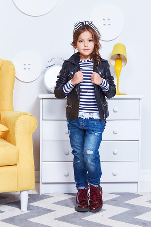 Fashion style clothes for child small little girl wear strip t-shirt denim jeans lather jacket boots hat bow cute pretty face curly hair baby model fun play room color furniture yellow chair toy game.