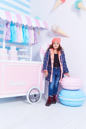Small little girl beautiful lady curly hair child cute face smile sweets baby shower party candy bar game room birthday wear funny clothes hat jacket denim jeans toy play fun hold pillow star clothes.