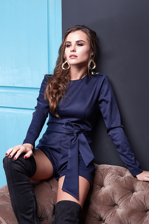 Beautiful sexy lady brunet hair spring autumn collection fashion clothes for date party success business woman wear short dark blue sit on the sofa room interior blue door luxury style accessory. Foto de archivo