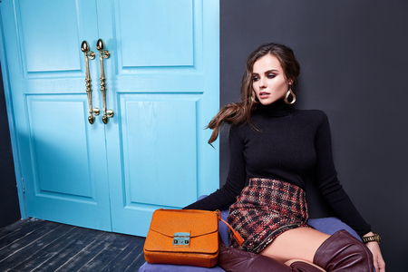 Beautiful sexy lady long brunet hair spring autumn collection fashion clothes for date party success business woman wear skirt black sweater shoes sit on sofa room interior luxury style accessory bag. Stock Photo