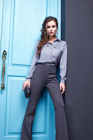 Sexy pretty woman beauty face cosmetic makeup hair wear fashion clothing style for business lady boss wear dress code pants blouse accessory bag jewelry interior blue door date party glamour model.
