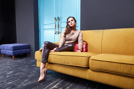 Sexy woman beauty makeup wear lather skinny pants cashmere wool sweater fashion clothing style for business lady accessory bag hand watch jewelry interior room furniture sofa blue door glamour model. 写真素材