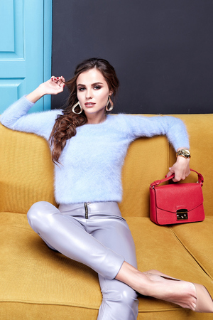 Sexy pretty woman beauty face cosmetic makeup long hair wear fashion clothing style for business lady boss pants sweater accessory bag jewelry interior room furniture sofa date party glamour model.