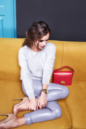 Sexy pretty woman beauty face cosmetic makeup long hair wear sweater pants fashion clothing style for business accessory lather bag jewelry earring interior furniture sofa date party glamour model.
