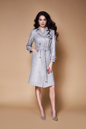 Beautiful sexy woman wear business style clothing for office casual meeting collection accessory cashmere wool coat jacket sexy glamor fashion model beauty face long brunette hair jewelry earrings. Фото со стока
