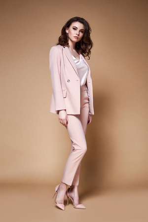 Sexy beautiful business woman lady boss CEO manager makeup long curly hair brunette wear clothes office dress code suit jacket pants uniform work or date catalog accessory jewelry elegant style. Foto de archivo