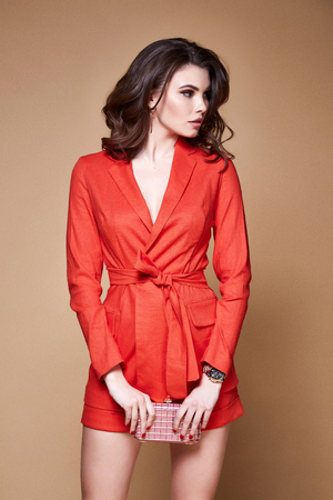 Sexy beauty woman pretty face tan skin wear orange suit jacket and short skinny body shape makeup cosmetic summer collection studio catalog brunette curly hair clothes date meeting walk party fashion. Stock Photo