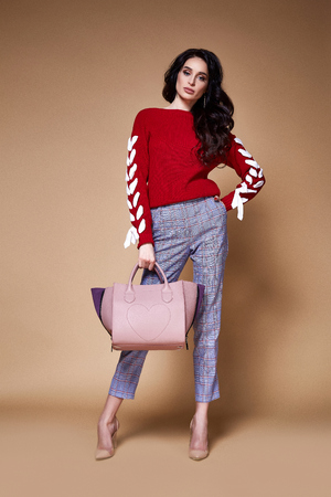 Sexy beauty woman pretty face skin wear red cotton cashmere sweater pants body shape makeup accessory bag style collection studio catalog brunette curly hair clothes date meeting walk party fashion.
