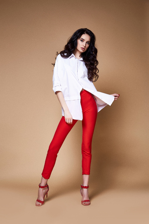 Sexy beautiful woman pretty face makeup cosmetic face care dark curly hair brunette wear clothes cotton oversize blouse skinny red jeans date or party catalog spring collection accessory jewelry.