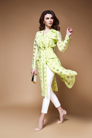 Sexy beauty woman pretty face tan skin wear yellow silk dress trench long white pants makeup cosmetic collection studio catalog brunette curly hair clothes date party fashion style model pose lady.