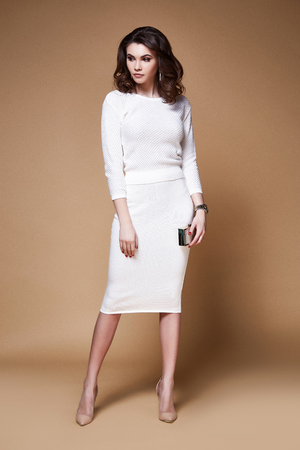 Sexy beauty woman pretty face tan skin wear white knitted dress long skinny body shape makeup cosmetic dress code collection studio catalog brunette curly hair clothes for date office party fashion.
