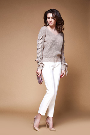 Sexy beauty woman pretty face young wear white pants beige sweater accessory bag businesswoman skinny body shape makeup studio catalog brunette curly hair clothes for date meeting work party fashion.