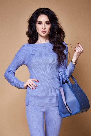 Sexy beautiful woman pretty face bright makeup cosmetic face care long curly hair brunette wear clothes blue knitted sport suit date or party catalog spring collection accessory bag sale magazine. Stock Photo