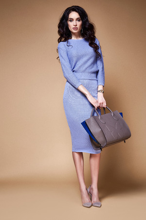 Sexy beauty woman pretty face tan skin wear blue knitted suit dress long skinny body shape makeup cosmetic summer collection studio catalog brunette accessory bag clothes for office party fashion.