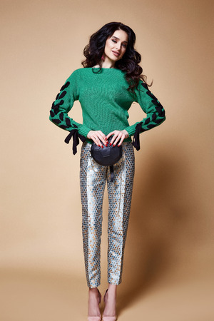 Sexy beautiful woman fashion glamour model brunette hair makeup wear knitted sweater green trousers clothes for every day casual party style jewelry date walk girlfriend skinny body shape studio.
