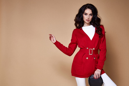 Portrait sexy beauty woman pretty face tan skin wear white knitted jacket red casual suit for every day makeup cosmetic spring collection studio catalog brunette curly hair clothes walk fashion. Stock Photo - 100857312