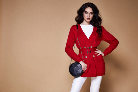 Portrait sexy beauty woman pretty face tan skin wear white knitted jacket red casual suit for every day makeup cosmetic spring collection studio catalog brunette curly hair clothes walk fashion. Stock Photo