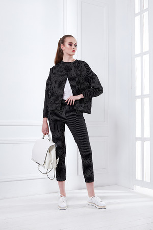 Beautiful sexy young business woman blond hair with evening makeup wearing a dress code black suit pants jacket top and sport shoes business clothes for meetings and walks collection accessory bag. Stock Photo