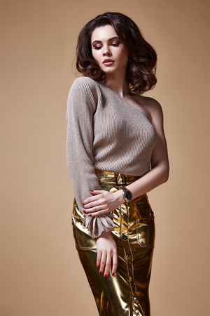 Sexy beauty woman pretty face tan skin wear sweater gold skirt body shape makeup cosmetic summer collection studio catalog brunette curly hair clothes date meeting walk party fashion shoes accessory. Stock Photo