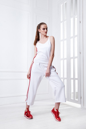 Sexy pretty beautiful woman fashion style clothes model perfect face wear white sport casual suit top trousers sneakers hair accessory catalog designer clothes party walk interior room light window.