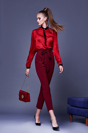 Beautiful sexy pretty woman wear red silk blouse and pants skinny body shape lady boss business woman skin tan long brunette hair party style fashion cloches accessory jewelry earrings studio sofa.